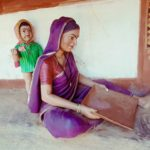 tribal lady cleaning raagi with her baby