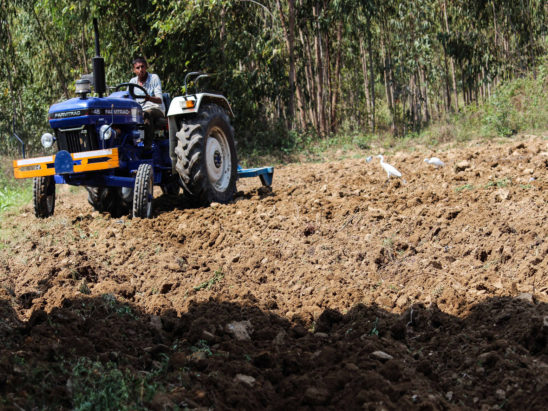 Farmer Cultivating Agricultural Land using Tractor
