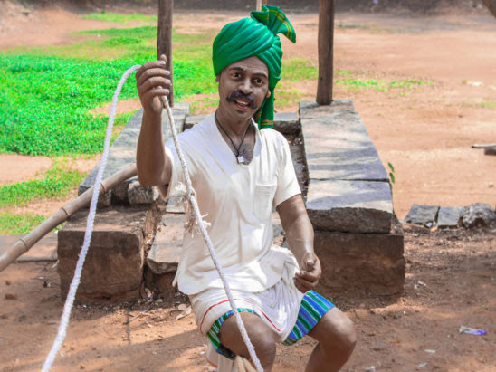 Farmer holding rope of bullock cart