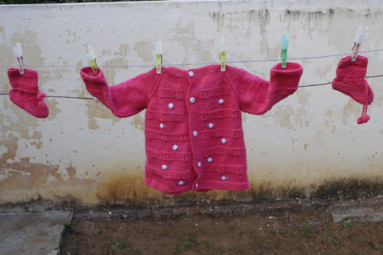 pink sweater and socks hanging - baby dress
