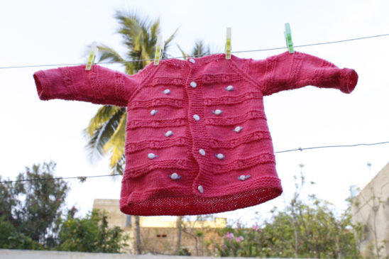 pink sweater hanging - baby dress