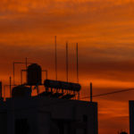 sunset - evening water tanks and solar heater