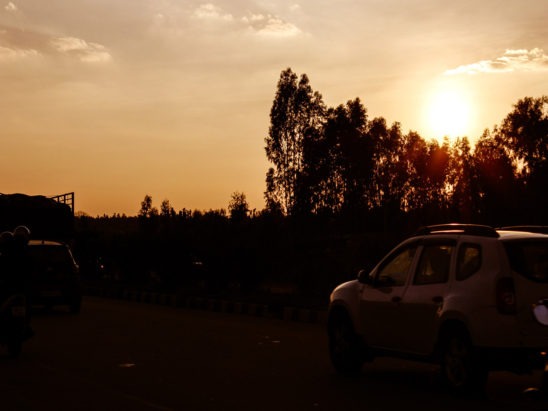 vehicles on road during sunrise